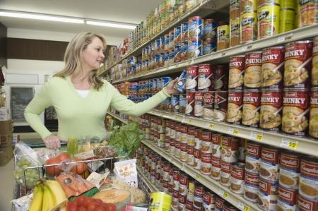 selects: Donna matura sceglie merce in scatola in un supermercato navata LANG_EVOIMAGES
