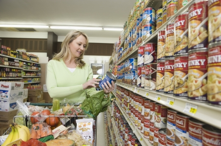 tinned goods: Mature woman selects tinned goods in supermarket aisle