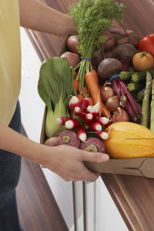unknown age: Woman holding container full of fresh vegetables mid section close-up