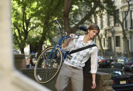 descending: Man carrying bicycle descending steps LANG_EVOIMAGES