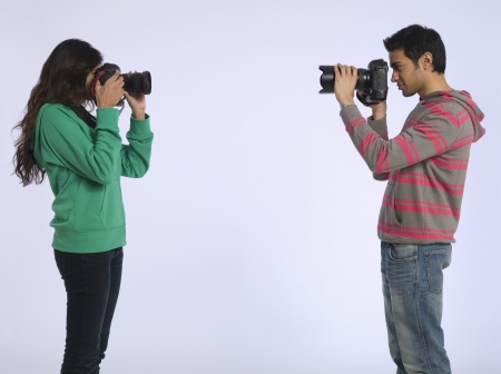 peo: Young woman and young man photographing each other studio shot LANG_EVOIMAGES
