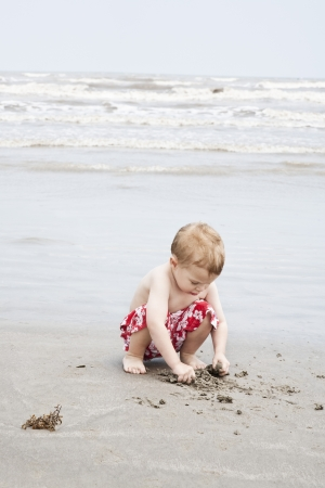 waters  edge: Boy crouching and playing with sand at waters edge LANG_EVOIMAGES