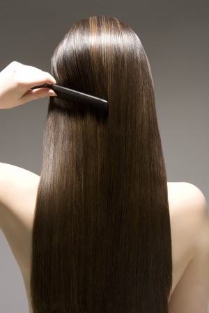 hair straight: Donna che pettina vista capelli lunghi castani retro LANG_EVOIMAGES
