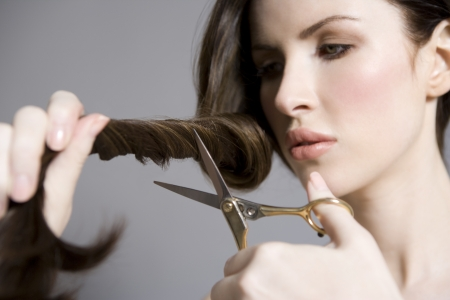 end of a long day: Woman cutting long brown hair