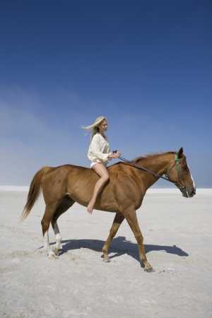 horse blonde: Mid-adult woman riding horse on beach LANG_EVOIMAGES