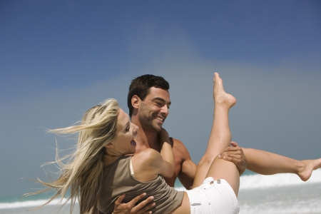 man carrying woman: Man carrying woman on beach laughing