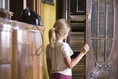fas: Girl opening cupboard door