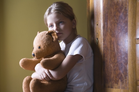 Girl embracing teddy bear in home