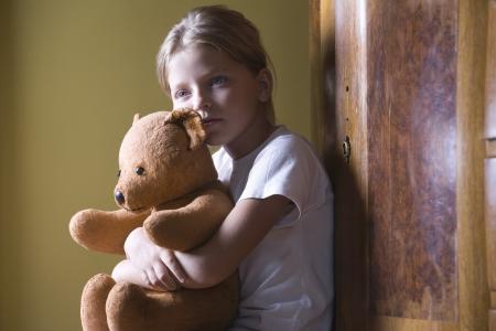 teddy bear: Muchacha que abraza el oso de peluche en casa LANG_EVOIMAGES