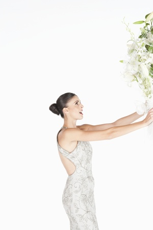 accepts: Woman in evening dress accepts a bouquet of white flowers