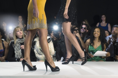 high fashion model: Low section of women walking in black high heeled shoes on fashion catwalk