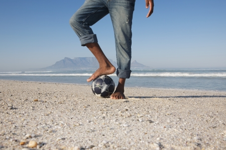 unknown age: Mans foot on soccer ball beach scene LANG_EVOIMAGES