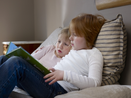 Two sisters sit reading on a single bed Stock Photo