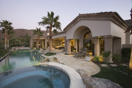 showhome: Luxury swimming pool and house exterior at dusk