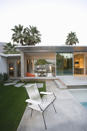 showhome: Empty chair on paved poolside area of Palm Springs home