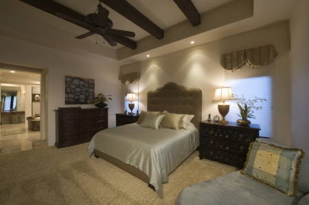 en suite: Silk bed cover on double bed in Palm Spring bedroom with beamed ceiling