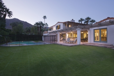 showhome: Lawn and swimming pool with lit exterior of Palm Springs home exterior