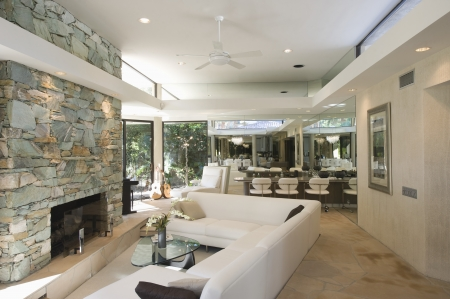 stone  fireplace: Sunken seating area and exposed stone fireplace of Palm Springs home interior
