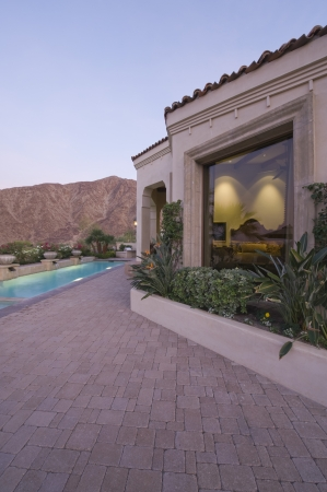 showhome: Paved poolside area and window exteriors of Palm Springs home