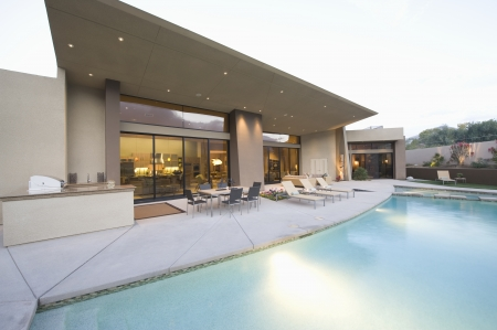 showhome: Swimming pool and paved seating area of Palm Springs home exterior