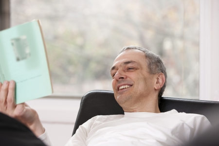 40 to 45 year olds: Mid adult man relaxing at home reading a book LANG_EVOIMAGES