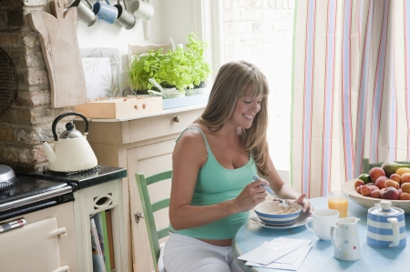 only one woman: Pregnant woman sitting at kitchen table eating breakfast