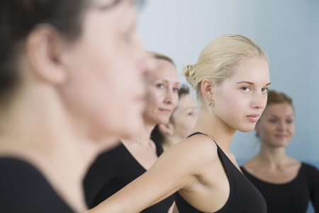 one person with others: Young women in ballet rehearsal