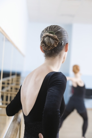 a rehearsal: Young woman stands at barre in ballet rehearsal room