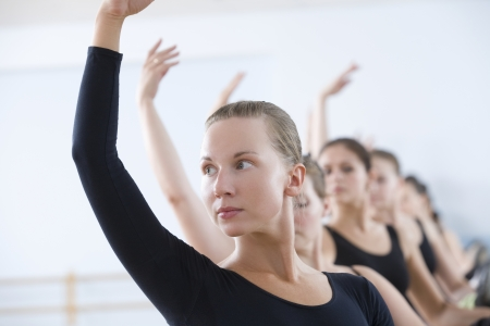 20s adult: Young women with arms raised at the barre LANG_EVOIMAGES