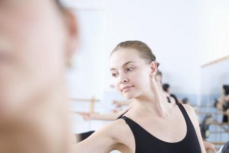 one person with others: Young woman stretches into ballet pose LANG_EVOIMAGES