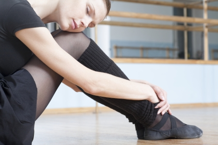 leg warmers: Young woman sits resting in rehearsal room LANG_EVOIMAGES