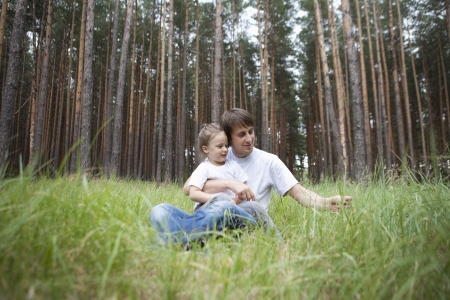 abducted: Man and girl sit in woodland clearing LANG_EVOIMAGES