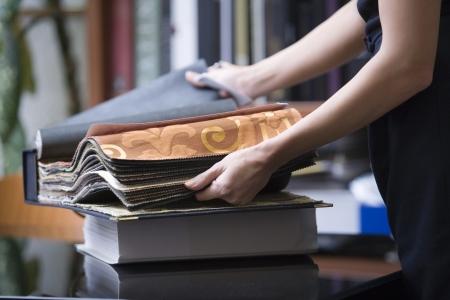 interior designer: Young designer looks through sample book