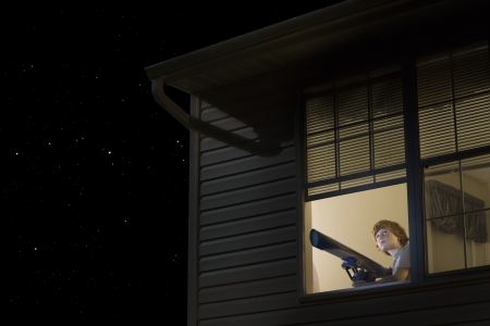 open window: Teenage boy with telescope at open window looking at night sky