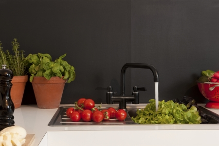 ingredients tap: Fresh salad ingredients on kitchen sink