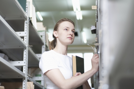 shelving: Young woman stands at library shelving LANG_EVOIMAGES