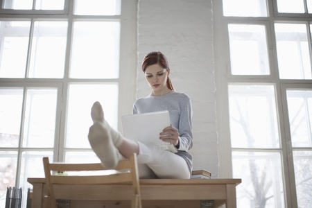 feet on desk: Woman sits on desk with laptop in loft apartment