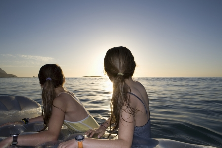 Twin sisters on air bed look back at land