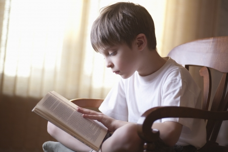 one boy only: Boy sits cross-legged on chair reading book
