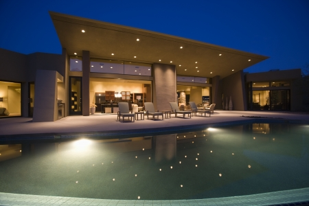 Lit swimming pool and house exterior at night Stock Photo