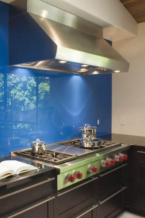 fitted unit: Blue splashback and stainless steel extractor fan