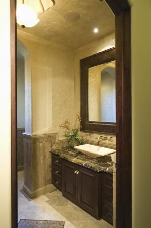 view through: View through doorway to dark wood bathroom with leather mirror frame