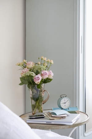 'bedside table': Roses in vase on bedside table with books and alarm clock