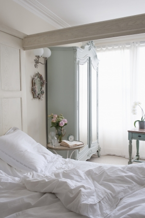 unmade: Unmade bed in sunlit beamed room LANG_EVOIMAGES
