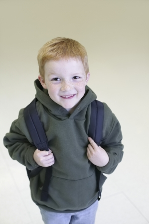 casual hooded top: Schoolboy with redhair and freckles stands with backpack