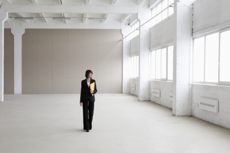 empty warehouse: Business woman stands in empty warehouse