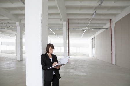 empty warehouse: Business woman leans against pillar with file in empty warehouse