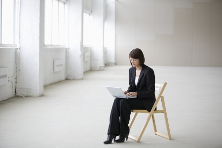 empty warehouse: Business woman works on laptop in empty warehouse