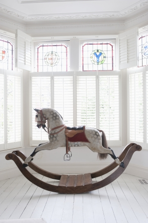Antique rocking horse in bay window with stained glass London 版權商用圖片