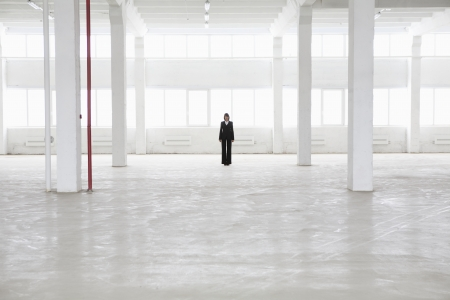 empty warehouse: Distant woman stands in empty warehouse